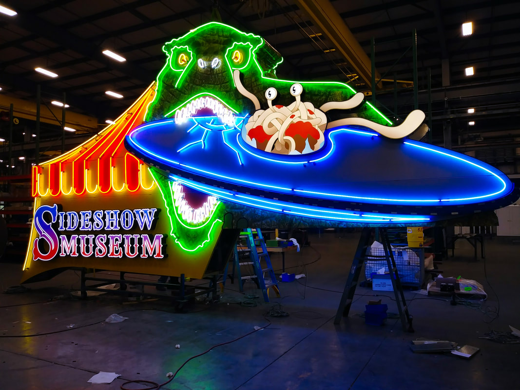 Large neon sign of dinosaur biting a flying saucer for Sideshow Museum